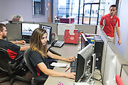 Monica Nezzer and Patrick Arite at their desks inside the Student Support Center where they work when not giving tours.  At right is coworker Alexander Gordon. Nezzer and Arite are students at the University of New Mexico and are working 15-30 hours per week giving campus tours in order to help put themselves through college. (Steven St. John for NPR)