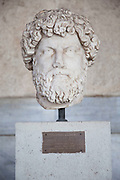 Carved marcle head from a statue entitled 'Portrait of a man' probably Aelius Verus at The Stoa of Attalos or Attalus located in the east side of archaeological site of the Ancient Agora in Athens just oposite the Adrianou street in Monastiraki. The Stoa of Attalos was built around 150 BC, by Attalos II, King of Pergamos as a donation to Athens. The construction of the building began in 159 BC and ended in 138 BC. The building was the largest in length in Greece during the antiquity. It was rebuilt in the same style and shape from 1953 to 1956 with beautifully crafted marble columns. It is recognised as one of the most impressive stoa in the Athenian Agora. Typical of the Hellenistic age, the stoa was more elaborate and larger than the earlier buildings of ancient Athens. The stoa's dimensions are 115 by 20 metres wide (377 by 65 feet wide) and it is made of Pentelic marble and limestone. The building skillfully makes use of different architectural orders. The Doric order was used for the exterior colonnade on the ground floor with Ionic for the interior colonnade. Athens is the capital and largest city of Greece. It dominates the Attica periphery and is one of the world's oldest cities, as its recorded history spans around 3,400 years. Classical Athens was a powerful city-state. A centre for the arts, learning and philosophy.