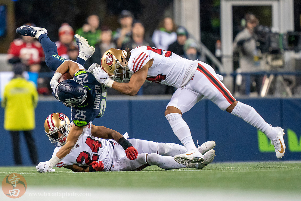 December 29, 2019; Seattle, Washington, USA; San Francisco 49ers middle linebacker Fred Warner (54) and defensive back K'Waun Williams (24) tackle Seattle Seahawks running back Travis Homer (25) during the second quarter at CenturyLink Field.
