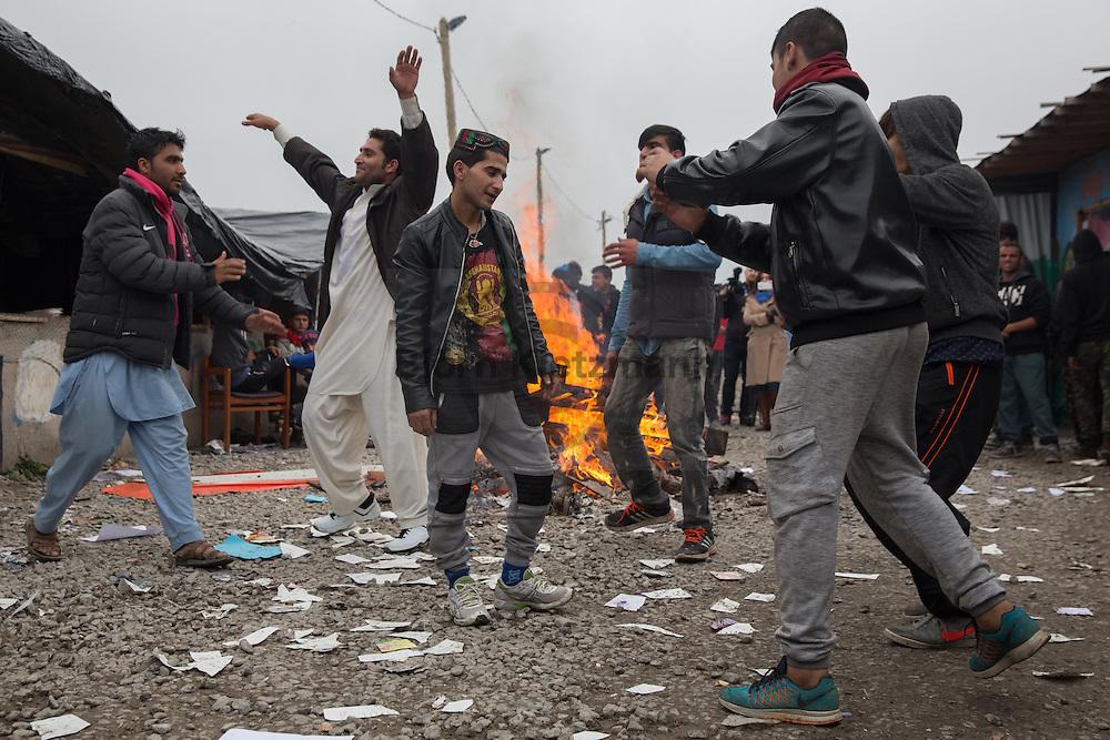 """Calais, Pas-de-Calais, France - 24.10.2016    <br />  <br /> Young refugees dance arround a fire. Start of the eviction on the so called """"Jungle"""" refugee camp on the outskirts of the French city of Calais. Refugees and migrants leaving the camp to get with buses to asylum facilities in the entire country. Many thousands of migrants and refugees are waiting in some cases for years in the port city in the hope of being able to cross the English Channel to Britain. French authorities announced a week ago that they will evict the camp where currently up to up to 10,000 people live.<br /> <br /> Junge Fluechtlinge tanzen um ein Feuer herum. Beginn der Raeumung des so genannte """"Jungle""""-Fluechtlingscamp in der französischen Hafenstadt Calais. Fluechtlinge und Migranten verlassen das Camp um mit Bussen zu unterschiedlichen Asyleinrichtungen gebracht zu werden. Viele tausend Migranten und Fluechtlinge harren teilweise seit Jahren in der Hafenstadt aus in der Hoffnung den Aermelkanal nach Großbritannien ueberqueren zu koennen. Die franzoesischen Behoerden kuendigten vor einigen Wochen an, dass sie das Camp, indem derzeit bis zu bis zu 10.000 Menschen leben raeumen werden. <br /> <br /> Photo: Bjoern Kietzmann"""