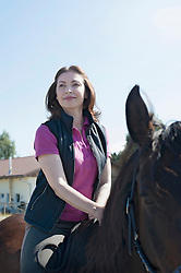 Mature woman riding a horse in farm and smiling, Bavaria, Germany