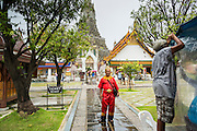 """23 SEPTEMBER 2013 - BANGKOK, THAILAND:  Tourists pose for pictures dressed in costumes of the Royal Thai court circa 1800 in front of the central prang at Wat Arun. The outstanding feature of Wat Arun is its central prang (Khmer-style tower). The world-famous stupa will be closed for three years to undergo repairs and renovation along with other structures in the temple compound. This will be the biggest repair and renovation work on the stupa in the last 14 years. In the past, even while large-scale work was being done, the stupa used to remain open to tourists. It may be named """"Temple of the Dawn"""" because the first light of morning reflects off the surface of the temple with a pearly iridescence. The height is reported by different sources as between 66,80 meters and 86 meters. The corners are marked by 4 smaller satellite prangs. The temple was built in the days of Thailand's ancient capital of Ayutthaya and originally known as Wat Makok (The Olive Temple). King Rama IV gave the temple the present name Wat Arunratchawararam. Wat Arun officially ordained its first westerner, an American, in 2005. The central prang symbolizes Mount Meru of the Indian cosmology. The temple's distinctive silhouette is the logo of the Tourism Authority of Thailand.          PHOTO BY JACK KURTZ"""