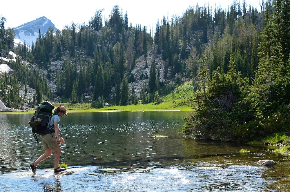 Backpacker crossing on stones, Moccasin Lake, Wallowa Mountains, Oregon.