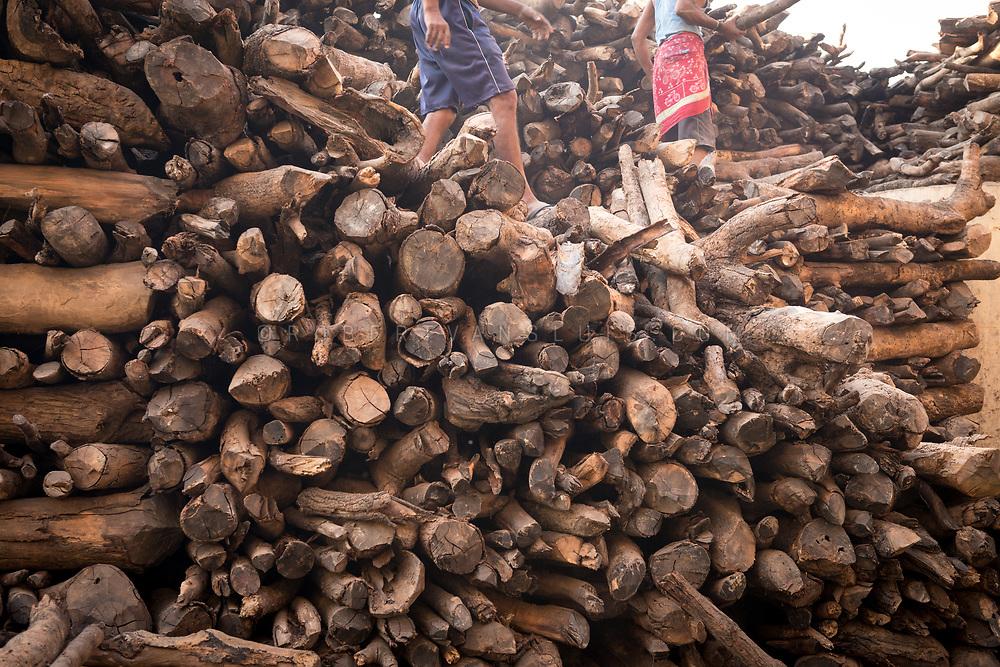 Two men sort out a pile of firewood near Manikarnika cremation ground, Varanasi, India. Photo ©robertvansluis.com