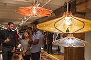 Light fixtures made of plywood frames and woven string on display in the booth of Wake Up Dear. Designer Suzuko Hisata is ion the center of the group on the left.
