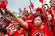 17 MAY 2014 - BANGKOK, THAILAND: Red Shirt supporters sing the Thai national anthem during a Red Shirt rally on Aksa Rd in Bangkok. Thousands of Thai Red Shirts, members of the United Front for Democracy Against Dictatorship (UDD), members of the ruling Pheu Thai party and supporters of the government of ousted Prime Minister Yingluck Shinawatra are rallying on Aksa Road in the Bangkok suburbs. The government was ousted by a court ruling earlier in the week that deposed Yingluck because the judges said she acted unconstitutionally in a personnel matter early in her administration. Thailand now has no functioning government. Red Shirt leaders said at the rally Saturday that any attempt to impose an unelected government on Thailand could spark a civil war. This is the third consecutive popularly elected UDD supported government ousted by the courts in less than 10 years.    PHOTO BY JACK KURTZ