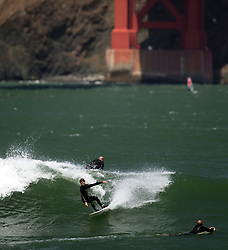 Unidentified surfers ride the waves as they roll in off the Pacific Ocean, near Fort Point at the southern end of the Golden Gate Bridge, Monday, April 13, 2015, in San Francisco. (Photo by D. Ross Cameron)