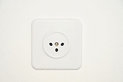 Standard Israeli three prong electric socket on white wall