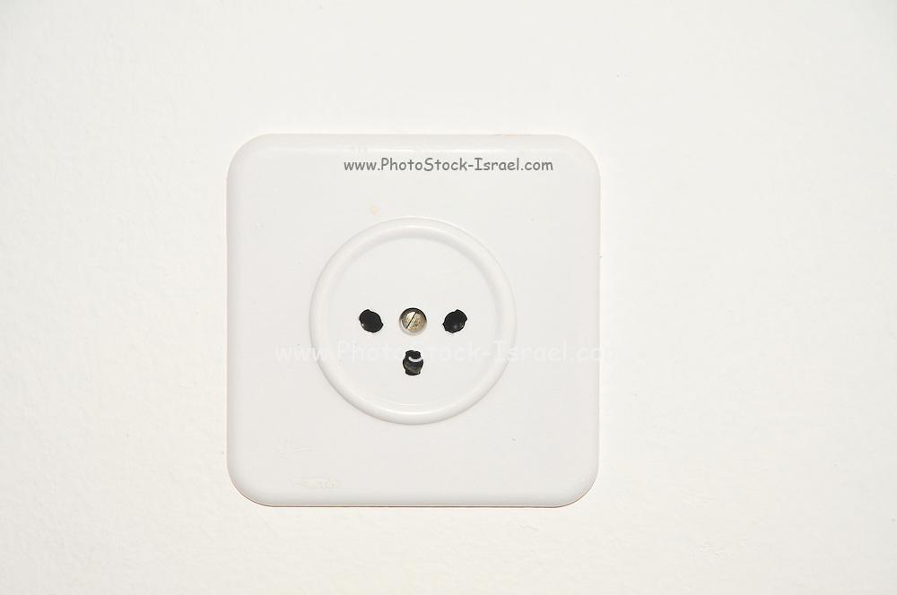 Standard Israeli three prong electric socket on white wall