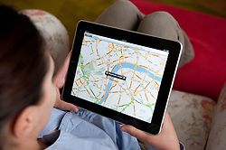 Woman using Google Maps application on iPad tablet computer to look at map of London