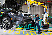 SAN LUIS POTOSI, MEXICO - JUNE 13, 2019: A worker places the tires of the cars in the BMW vehicles production plant in Mexico.