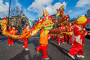 Large crowds watch a dragon dance at Cambridge Circus - Chinese New Year Celebrations in London 2018 marking the arrival of the Year of the Dog. The Event started with a Grand Parade from the North East side of the Trafalgar Square and finishing in Chinatown at Shaftesbury Avenue. It was organised by London Chinatown Chinese Association and is supported by The Mayor of London and Westminster City Council.
