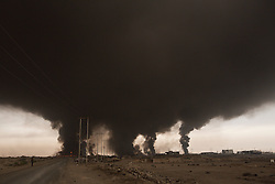 Licensed to London News Pictures. 08/11/2016. Qayyarah, Iraq. Smoke from a burning oil facility fills the sky over the Iraqi town of Qayyarah. Oil wells in and around the town of Qayyarah, Iraq, we set alight in July 2016 by Islamic State extremists as the Iraqi military began an offensive to liberated the town.<br /> <br /> For two months the residents of the town have lived under an almost constant smoke cloud, the only respite coming when the wind changes. Those in the town, despite having been freed from ISIS occupation, now live with little power, a water supply tainted with oil that only comes on periodically and an oppressive cloud of smoke that coats everything with thick soot. Many complain of respiratory problems, but the long term health implications for the men, women and children living in the town have yet to be seen. Photo credit: Matt Cetti-Roberts/LNP