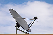 satellite television dish antenna pointing into a cloudy blue sky <br />