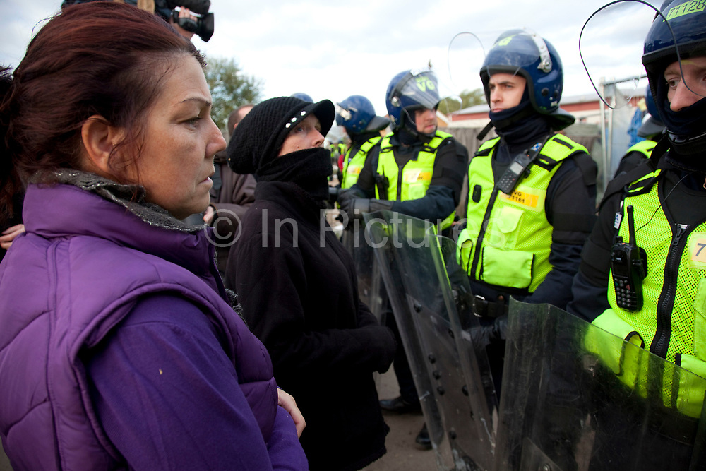 Traveller faces a line of riot police. Travellers at Dale Farm site prior to eviction. Riot police and bailiffs were present on 20th October 2011, as the site was cleared of the last protesters chained to barricades. Dale Farm is part of a Romany Gypsy and Irish Traveller site in Crays Hill, Essex, UK<br /> <br /> Dale Farm housed over 1,000 people, the largest Traveller concentration in the UK. The whole of the site is owned by residents and is located within the Green Belt. It is in two parts: in one, residents constructed buildings with planning permission to do so; in the other, residents were refused planning permission due to the green belt policy, and built on the site anyway.