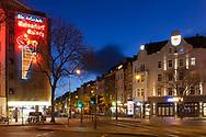 curfew from 9 pm during corona pandemic lockdown on May 5th. 2021. The deserted Aachener street at Rudolfplatz square, neon sign of the Reissdorf brewery, Cologne, Germany.<br /> <br /> Ausgangssperre ab 21 Uhr waehrend des Corona Lockdowns am 5. Mai 2021. Die menschenleere Aachener Strasse am Rudolfplatz, Neonreklame der Reissdorf Brauerei, Koeln, Deutschland.