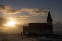People silouetted outside Víkurkirkja Church at sunset in winter. Vík, South Iceland.