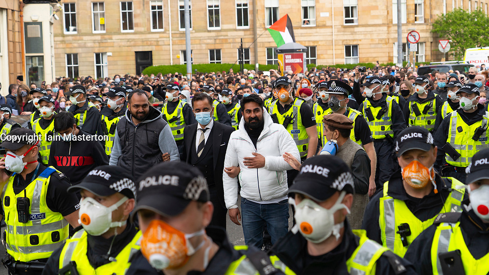 Glasgow, Scotland, UK. 13 May 2021.At approx 5.30 pm police released two men from a Home Office detention vehicle. Accompanied by lawyer Aamer Anwar the men walked to a nearby mosque surrounded by hundreds of police and supporters who had previously been surrounding the vehicle and sitting on the street. Two males surrounded by heavy police escort and hundreds of protesters  walk to mosque accompanied by Aamer Anwar. Iain Masterton/Alamy Live News