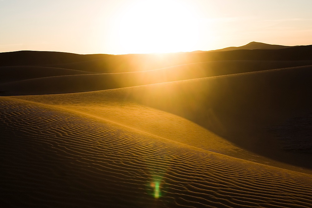The sun sets over the large and expansive sand dunes of Erg Zehar, near M'hamid, Morocco.