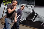 Men pass a Nike retail poster of Northern Irish golfer Rory McIlroy, in central London.  The two males walk past in good humour, one inhaling from his cigarette - the symbol of an unhealthy lifestyle versus the machismo character of athlete and sports hero. The scene has a theme of smiles and smiling faces with the teeth of the British golfing hero, sponsored by the Nike brand.