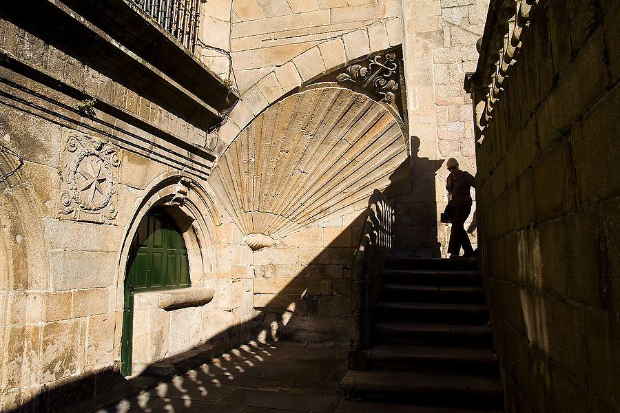 A woman walks down stairs leading out of the Cathedral and past a large scallop shell, symbol of Saint James, in Santiago de Compostela, Galicia, Spain.