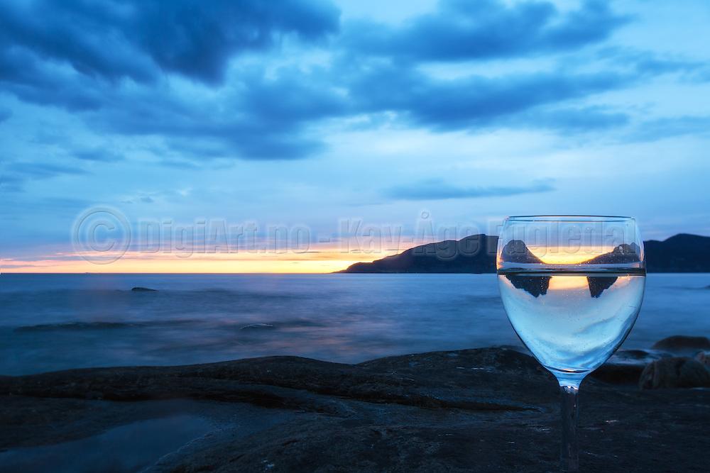 A glass at the shoreline, with sunset and reflection   Et glass i fjæra, med solnedgang og refleksjon.