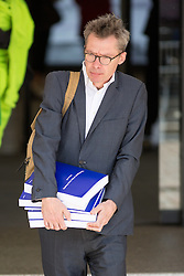 © Licensed to London News Pictures. 06/07/2016. London, UK. A man struggles to carry 4 volumes of a total 12 volumes of Sir John Chilcot's Report of the Iraq Inquiry. Chilcot is due to make a statement to the public later today. The Inquiry was predicated to take approximately one year, but has taken seven. Photo credit : Tom Nicholson/LNP