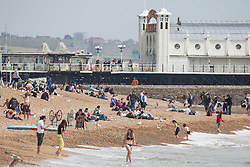 © Licensed to London News Pictures. 28/05/2021. Brighton, UK. Members of he public  enjoy warm afternoon along Brighton Beach in East Sussex. High temperatures of 24 degrees are expected in the South East of England this bank holiday, according to the Met Office. Photo credit: Marcin Nowak/LNP