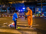 29 FEBRUARY 2016 - BANGKOK, THAILAND: A woman gives alms to a Buddhist monk in the middle of the street in front of the Bangkok flower market early Monday. Normally the sidewalk in the background is crowded with flower stands. Many of the sidewalk vendors around Pak Khlong Talat, the Bangkok flower market, closed their stalls Monday. As a part of the military government sponsored initiative to clean up Bangkok, city officials announced new rules for the sidewalk vendors that shortened their hours and changed the regulations they worked under. Some vendors said the new rules were confusing and too limiting and most vendors chose to close Monday rather than risk fines and penalties. Many hope to reopen when the situation is clarified.    PHOTO BY JACK KURTZ
