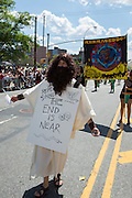"""A bearded man wearing biblical-looking robes wears a sign saying """"Repent sinners the end is near."""" Behind him is a banner reading """"Mermageddon."""""""