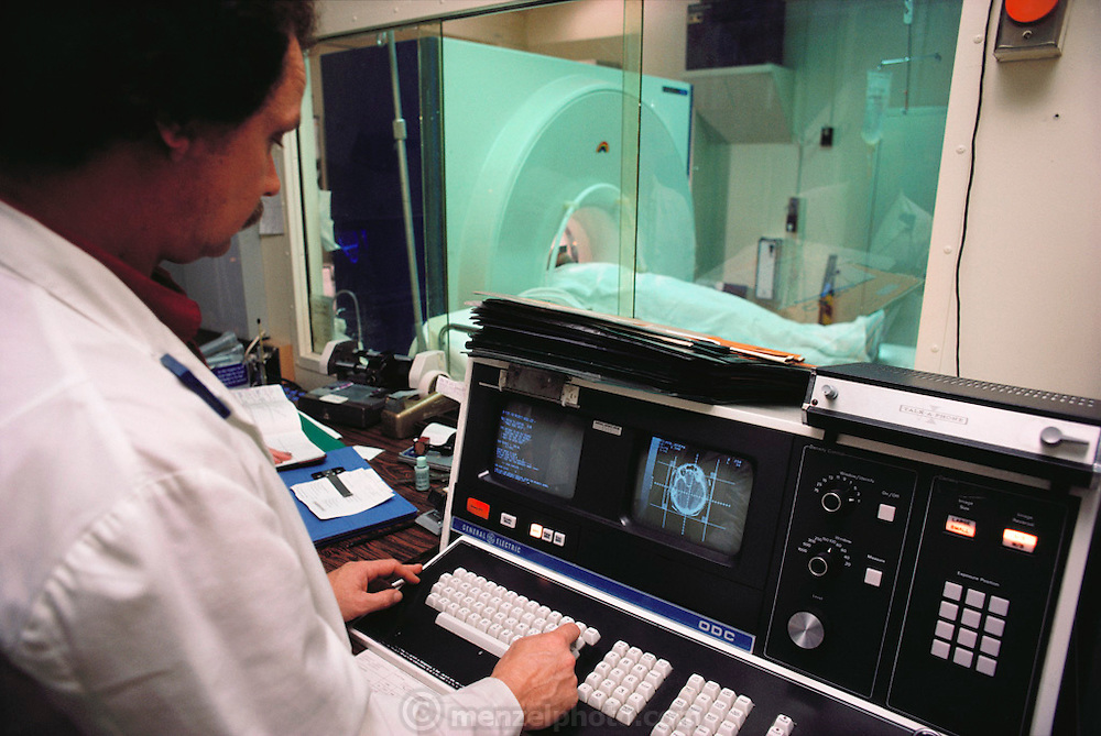 A scan operator monitors a patient who is having a CAT (computer-aided tomography) scan of a brain tumor. (1983)