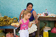 09 JANUARY 2007 - GRANADA, NICARAGUA:  A street vendor makes change for a child who bought an orange in Granada, Nicaragua. Granada, founded in 1524, is one of the oldest cities in the Americas. Granada was relatively untouched by either the Nicaraguan revolution or the Contra War, so its colonial architecture survived relatively unscathed. It has emerged as the heart of Nicaragua's tourism revival.  PHOTO BY JACK KURTZ