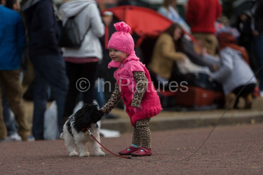 Child and dog celebrate their Queen's Diamnond Jubilee weeks before the Olympics come to London. The UK gears enjoys a weekend and summer of patriotic fervour as their monarch celebrates 60 years on the throne. Across Britain, flags and Union Jack bunting adorn towns and villages. This is a sweet picture of a child's innocence, her dream puppy perhaps the size of her toy dog at home. In the background are the crowds of public tents and celebration during an afternoon and evening of British festivities to commemorate the Queen's 60th anniversary of sovereign rule.