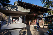 """A woman prays at Gotokuji Temple in Gotokuji, Satagaya, Tokyo, Japan. Friday January 11th 2019. Gotikuji Temple is famous as the supposed birthplace of the """"maneki neko"""" or  """"beckoning cat"""", which is a small white cat with one paw raised that is considered a lucky charm bringing customers and money into a business."""