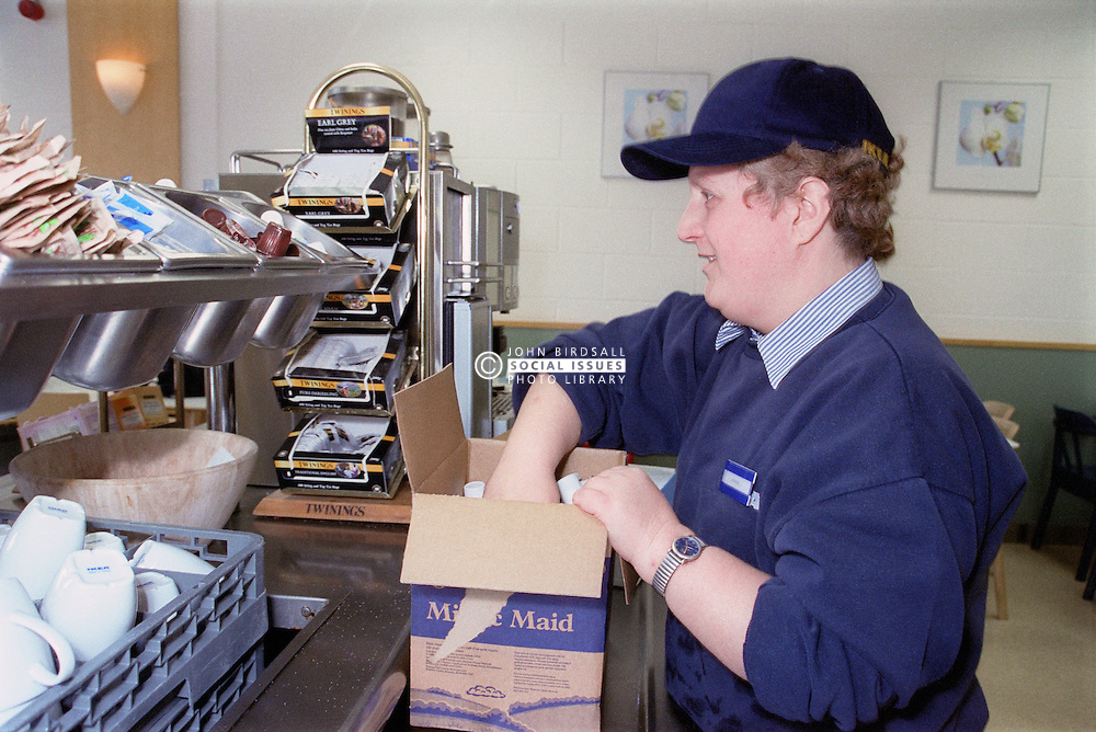 Woman with learning disability filling trays in canteen,
