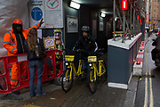 An Ofo employee pushes two rental bikes along a street, 24th January 2018, in London, England. ofo is a Beijing-based bicycle sharing company founded in 2014. It operates over 10 million yellow-colored bicycles in 250 cities and 20 countries, as of 2017. The dockless ofo system uses a smartphone app to unlock bicycles, charging an hourly rate for use. As of 2017, the company is valued at $3 billion and has over 62.7 million monthly active users.