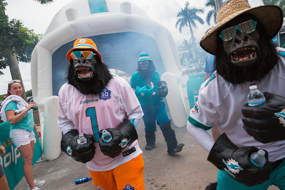 Miami Dolphins fans circulate in costume outside Sun Life Stadium on Sunday, Sept. 27, 2015, in Miami Gardens.