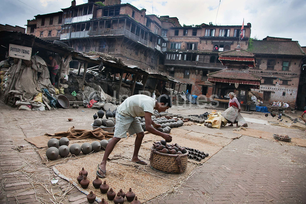 Pottery making is one of Bhaktapur's traditional industries and the pots are laid out in this little square to dry before going into the oven to be burned. Rain is coming and the pots are hurriedly taken inside.