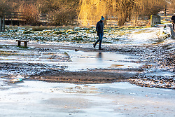 © Licensed to London News Pictures. 10/02/2021. London, UK. A walker avoids a frozen cycle path in Richmond Park, South West London this morning. The Met Office have issued weather warnings for extreme cold with temperatures forecast to drop to as low as -10c in London tonight as Storm Darcy continues to bring travel chaos to the South East and the rest of the UK.  Photo credit: Alex Lentati/LNP