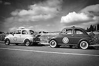 Black and white photo of two Fiat 500's in Florence Italy.