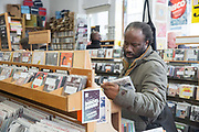 A man searching for CDs in a record shop on the 23rd March 2018 in Soho London in the United Kingdom.