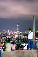 People gaze on the nighttime skyline of Taipei City in Taiwan.
