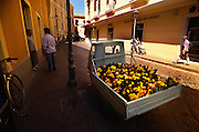 An old flower truck drives down a busy street in Sorento, Italy