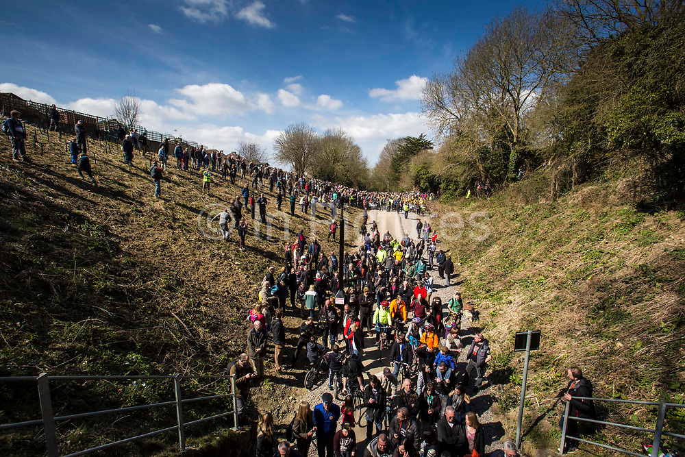 A landscape view of a large group of of enthusiastic people gather at the entrance and embankments of the Devonshire Tunnel for the official opening of the Bath Two Tunnels Greenway on 6th April 2013.  The 13 mile shared-path is a dramatic and accessible route leading south from Bath city and is accessible by foot, cycle, buggy and wheelchair. This development was started by a local community group and is part of the Sustrans lottery-funded project, Connect 2 Cycling Network. Sustrans is a charity that works with communities, policy-makers and partner organisations so that people can choose healthier, cleaner and cheaper journeys and enjoy better, safer spaces to live in. The event was attended by hundreds of cyclists and pedestrians of all ages and abilities. Bath,  Somerset, United Kingdom.