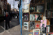 A visually impaired man with a white cane passes rare and second hand book shop window on Charing Cross Road on 18th February 2020 in London, England, United Kingdom. Charing Cross Road is renowned for its specialist and second-hand bookshops, and is home to many book shops, and more general second-hand and antiquarian shops.