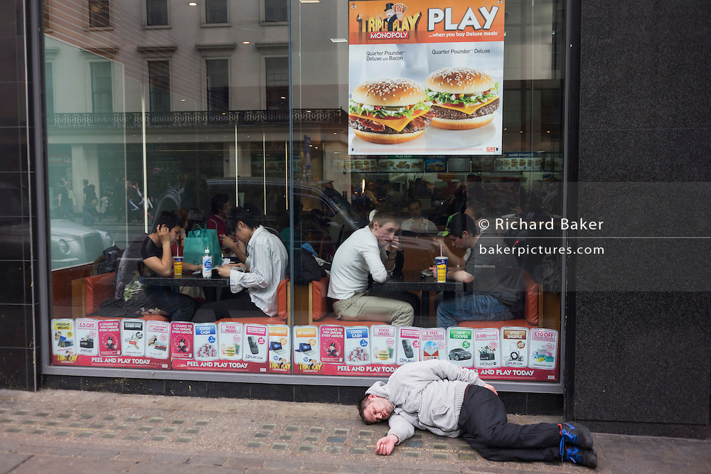 Diners ignore a man lying unconscious outside a McDonalds restaurant on a London street.