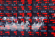 Lunchtime in the business district of Yaesu, as seen reflected off the stock quotation board window of Wako Securities Co. Ltd., Tokyo, 1999.<br /> <br /> © Torin Boyd 2003