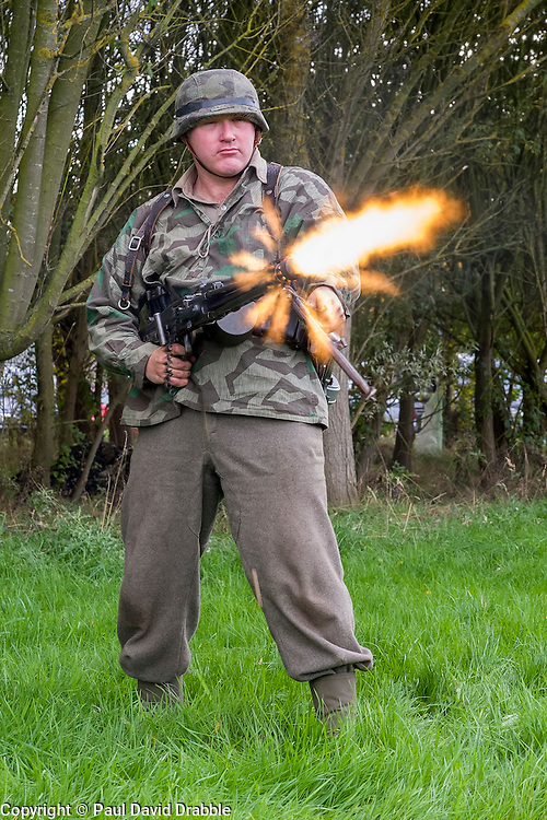 Re-encator portraying a German panzer grenadier test fires fires a 'section' 5 MG42 machinegun from the hip during the Pickering Wartime weekend on the Pickering Showground<br /> <br /> 17/18 October 2015<br />  Image © Paul David Drabble <br />  www.pauldaviddrabble.co.uk