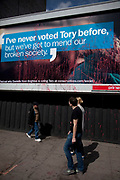 A Conservative Party billboard talking of mending our broken society is defaced with red paint. Whitechapel, London.