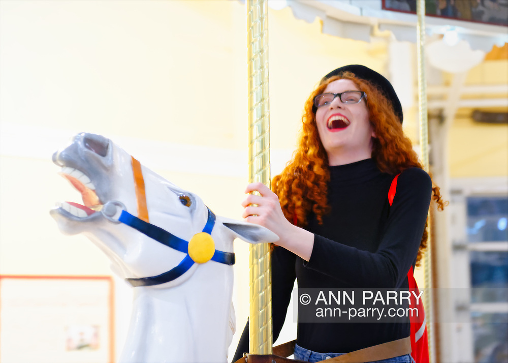 Garden City, New York, USA. March 9, 2019. CAYLA KEMPF, of Maspeth, Queens, is riding carousel horse during Unveiling Ceremony of Nunley's Carousel mural. The Kempf family is related to a silent partner of the carousel's original owners, the Murphy Brothers of Murphy's Carousel Company. Event was held at historic Nunley's Carousel in its Pavilion on Museum Row on Long Island.